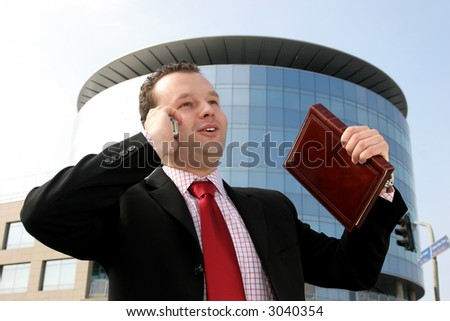 Happy young businessman talking on a cell phone and holding a notebook in front of a corporate building - stock photo