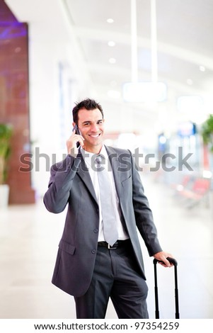 happy young businessman talking on cell phone at airport - stock photo