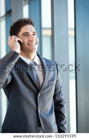 happy young businessman talking on mobile phone - stock photo