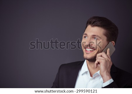 Happy Young Businessman Talking to Someone on Mobile Phone Against Dark Gray Wall Background with Copy Space on the Left Side. - stock photo