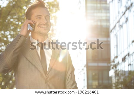 Happy young businessman using cell phone outdoors - stock photo