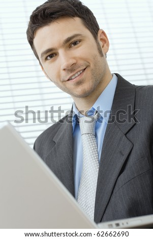 Happy young businessman using laptop computer at office, smiling. - stock photo