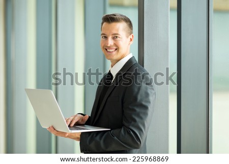 happy young businessman using laptop computer indoors - stock photo