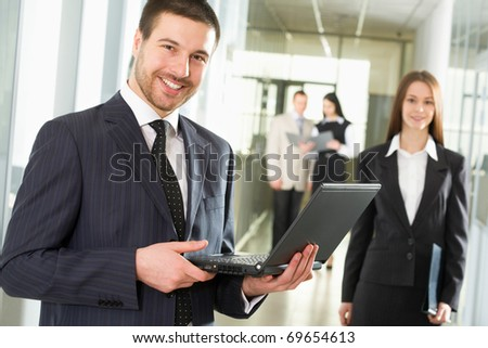 Happy young businessman using laptop in business building, - stock photo