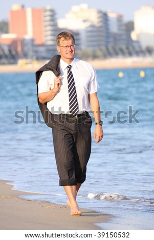 Happy young businessman walks close to the sea - stock photo