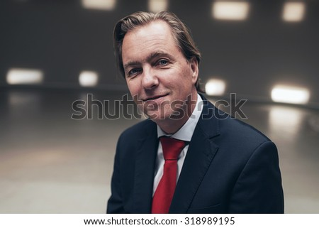Happy young businessman wearing suit with red tie in empty room.