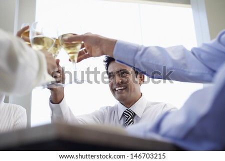 Happy young businessman with colleagues toasting wineglasses in restaurant - stock photo