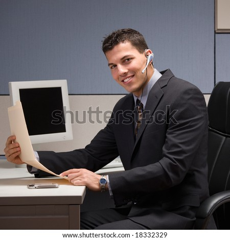 Happy young businessman with headset working at desk in cubicle - stock photo