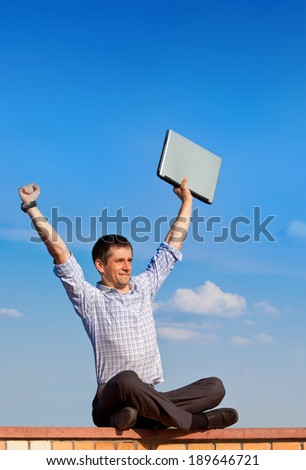 Happy young businessman with laptop  - stock photo