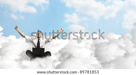 Happy young businessman with laptop sitting on the clouds. - stock photo