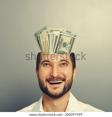 happy young businessman with open head looking up at money in his head and smiling over grey background - stock photo