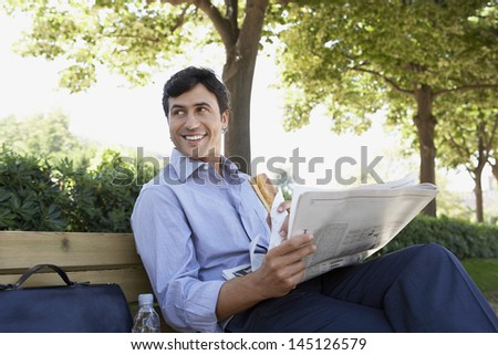 Happy young businessman with sandwich and newspaper looking away while sitting on bench outdoors - stock photo
