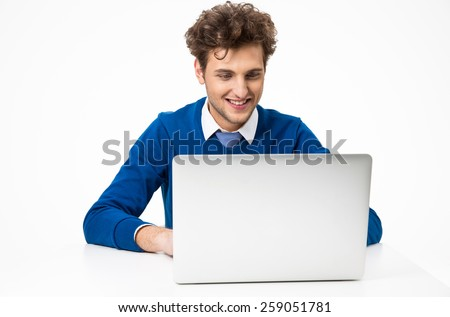 Happy young businessman working on the laptop
