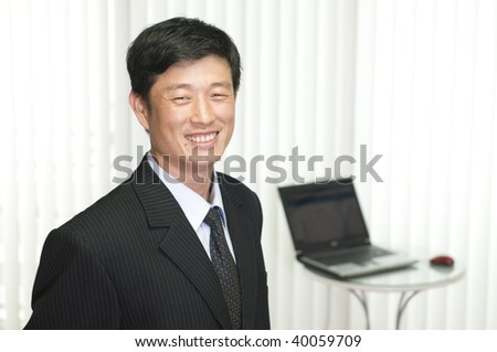 Happy young businessman, working with laptop in the office - stock photo