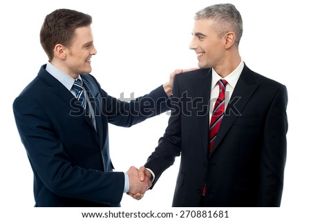 Happy young businessmen shaking hands - stock photo