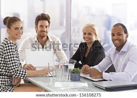 Happy young businesspeople sitting at meeting table, discussing business, smiling happy.