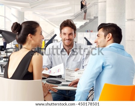 Happy young businessteam sitting at table, working together, smiling. - stock photo