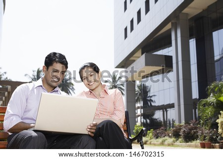 Happy young businesswoman and businessman using laptop outdoors - stock photo
