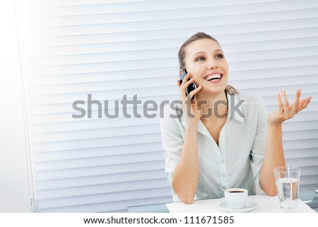 Happy young businesswoman answering phone call while sitting at table