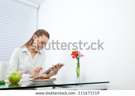 Happy young businesswoman browsing net on tablet PC while having breakfast