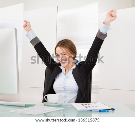 Happy Young Businesswoman Celebrating Success In The Office - stock photo