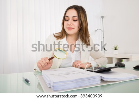 Happy Young Businesswoman Checking Bill With Magnifying Glass - stock photo