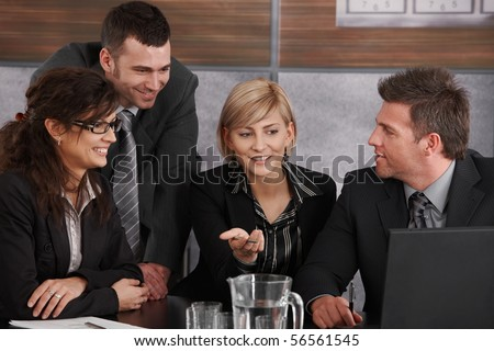 Happy young businesswoman explaining to partners, sitting at meeting table in office, others looking at her, smiling. - stock photo