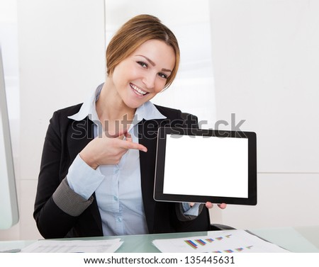 Happy Young Businesswoman Gesturing On Digital Tablet - stock photo