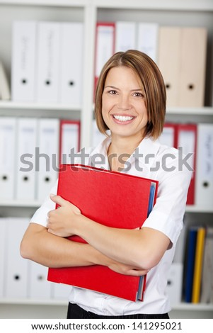 Happy young businesswoman holding a red binder - stock photo
