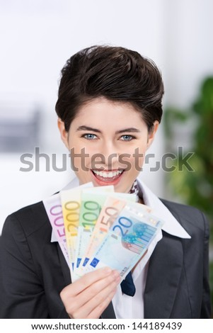 Happy young businesswoman holding fan of euro notes in office - stock photo