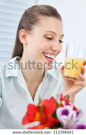 Happy young businesswoman holding glass of orange juice