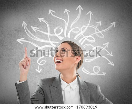 Happy, young businesswoman looking at many twisted arrows on the concrete wall overhead - stock photo
