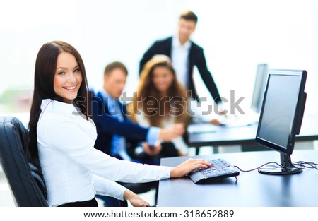 Happy young businesswoman looking behind and her colleagues working at office - stock photo