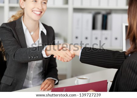 Happy young businesswoman shaking hands with candidate during an interview - stock photo