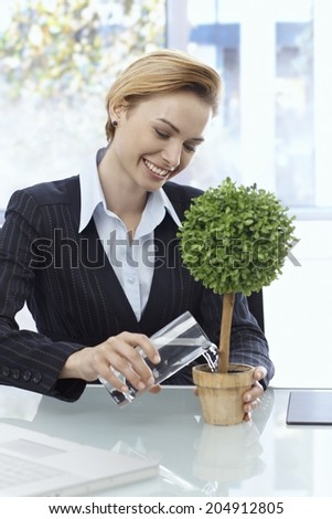 Happy young businesswoman sitting at desk, watering potted plant, smiling. - stock photo