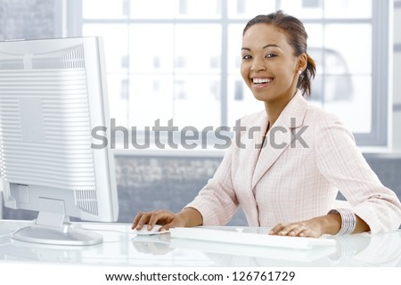 Happy young businesswoman sitting at desk, working on computer, laughing at camera. - stock photo