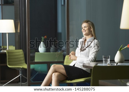 Happy young businesswoman sitting in office and smiling - stock photo
