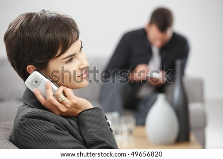Happy young businesswoman sitting on sofa at office talking on mobile phone, smiling. - stock photo