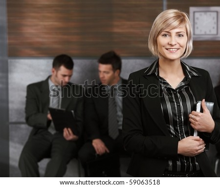 Happy young businesswoman standing in office hallway, holding personal organizer, smiling.? - stock photo