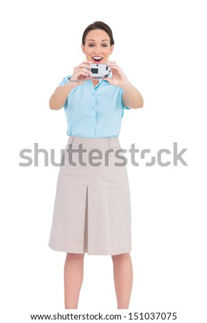 Happy young businesswoman taking picture of herself while posing on white background