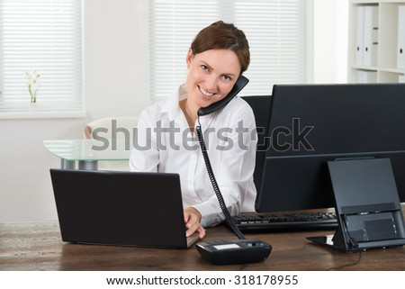 Happy Young Businesswoman Talking On Phone While Working On Laptop In Office - stock photo