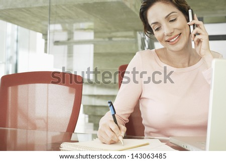 Happy young businesswoman using mobile phone while writing on notepad in office - stock photo