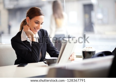 Happy young businesswoman using tablet computer in a cafe. Selective focus.