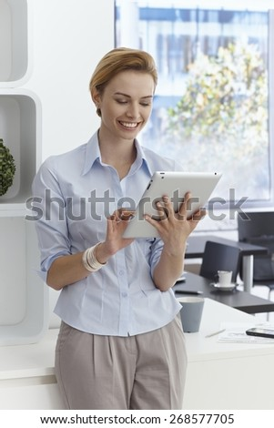 Happy young businesswoman using tablet computer, smiling. - stock photo