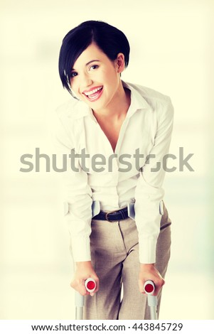 Happy young businesswoman with crutches - stock photo