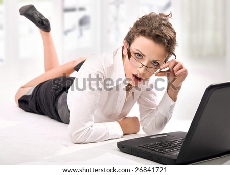 Happy young businesswoman with laptop looking attentively