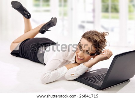 Happy young businesswoman with laptop on the floor - stock photo