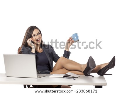 happy young businesswoman with legs on the table talking on the phone - stock photo