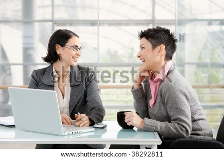 Happy young businesswomen working together at desk in modern office, looking at each other, laughing. - stock photo