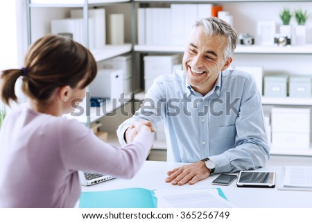 Happy young candidate shaking hands with her employer after a job interview, employment and business meetings concept - stock photo